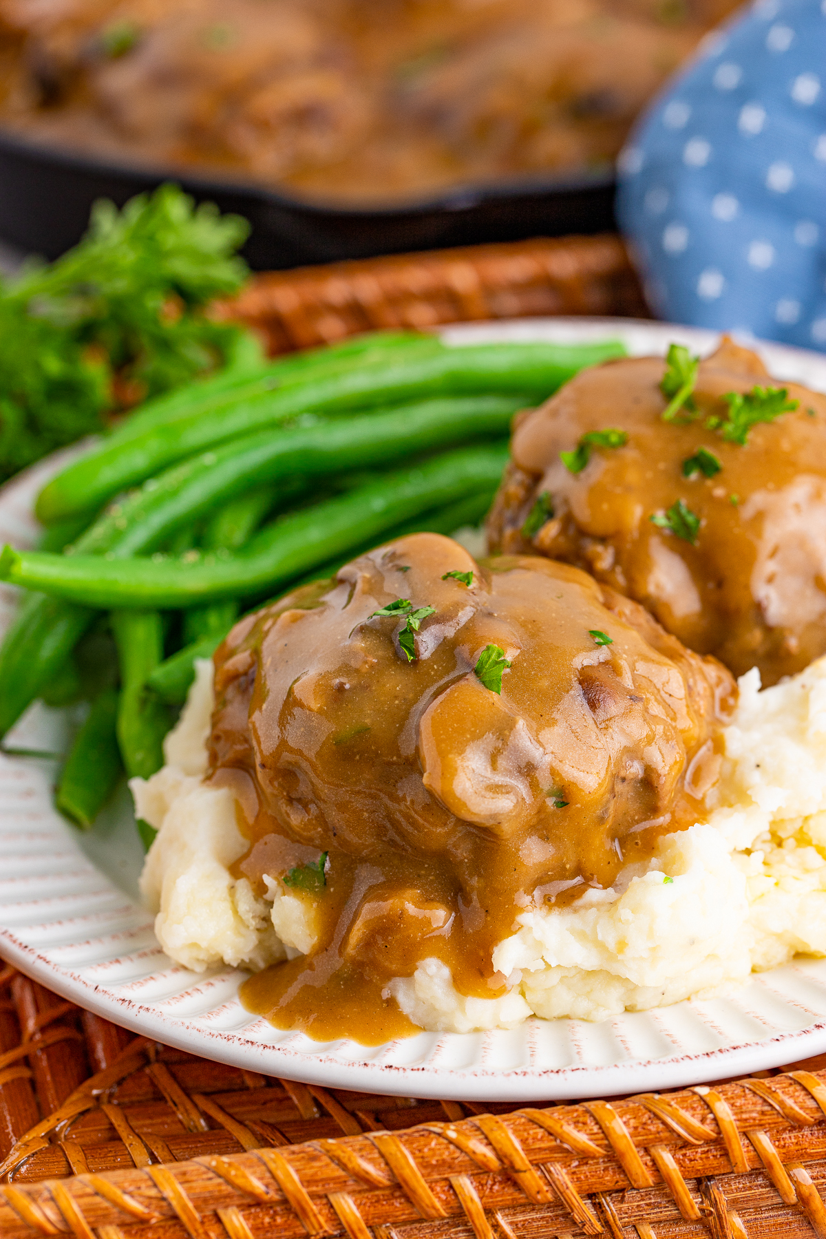 Salisbury Steak Recipe over potatoes with gravy and green beans on plate.