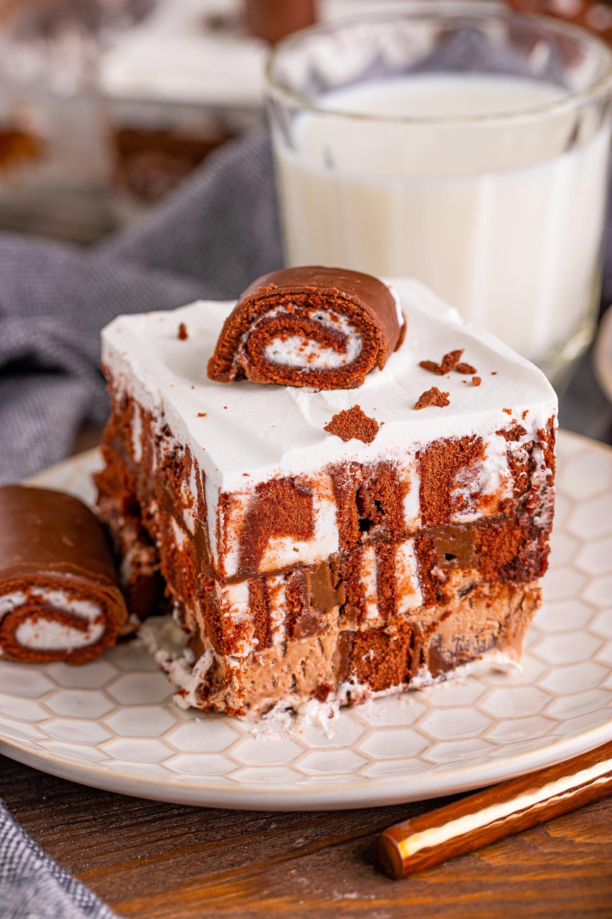 Slice of Swiss Cake Roll Lush Cake on patterned plate topped with slice of a swiss cake roll