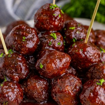 Square image of meatballs stacked with toothpicks.