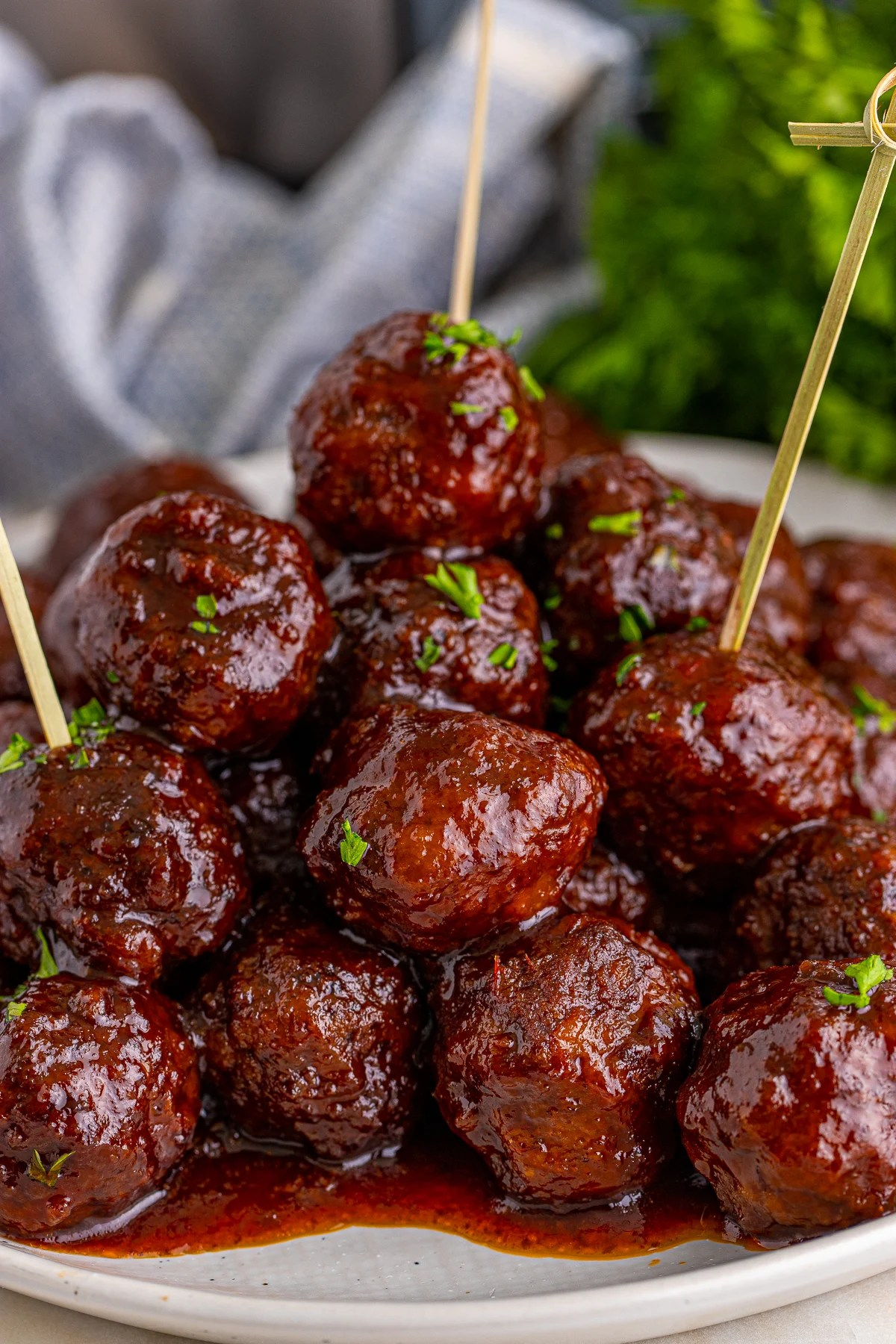 Stacked Crock Pot Grape Jelly Meatballs on plate with toothpicks.