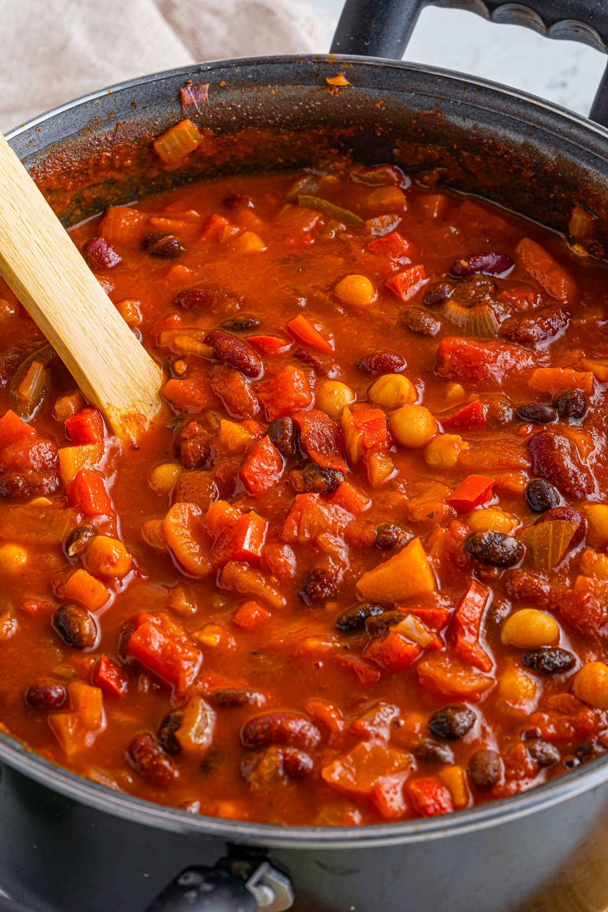 Close up in pot of fininshed Chili with woodenn spoon.