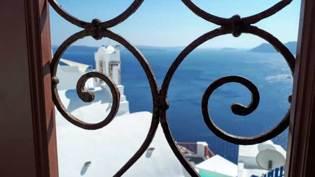 Close up of ornate metal gate, with white buildings and seaview behind it