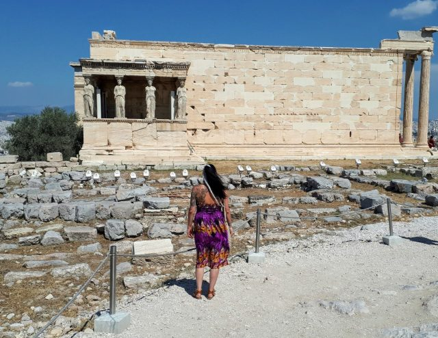 Back view of woman wearing purple and orange dress looking at the Temple of Athena