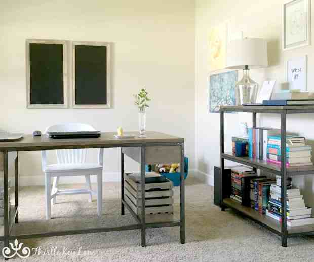 Home office with industrial looking desk and bookshelf.