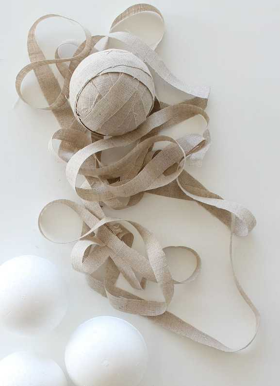 Strips of linen are used to cover a foam ball.