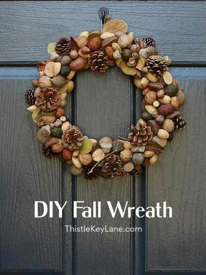 Fall wreath with pine cones and nutson a black door.