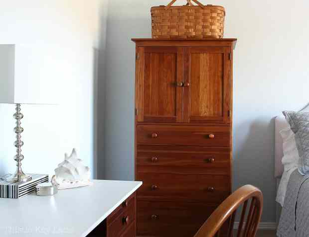 Armoire for storage in warm wood tones.