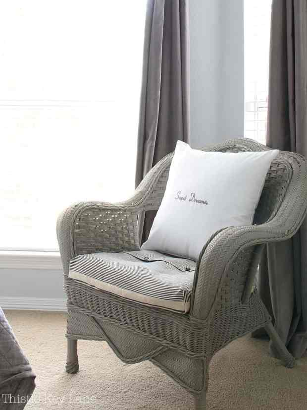 Wicker chair with striped ticking cushion.