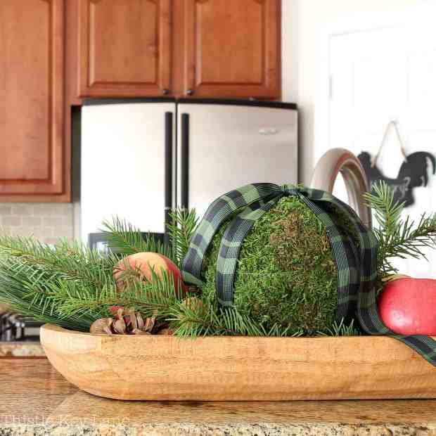 Fresh arrangement with moss, pine branches and apples.