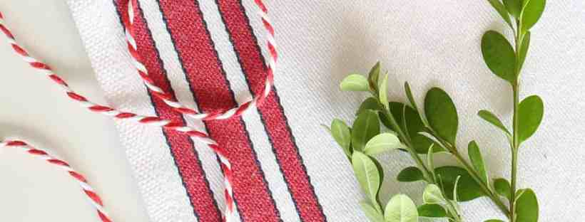 Cute red and white and boxwood are used to decorate a chair back.