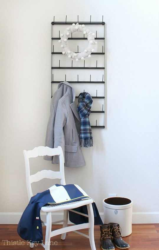 The coat rack in the entry is decorated with a sweater wreath.