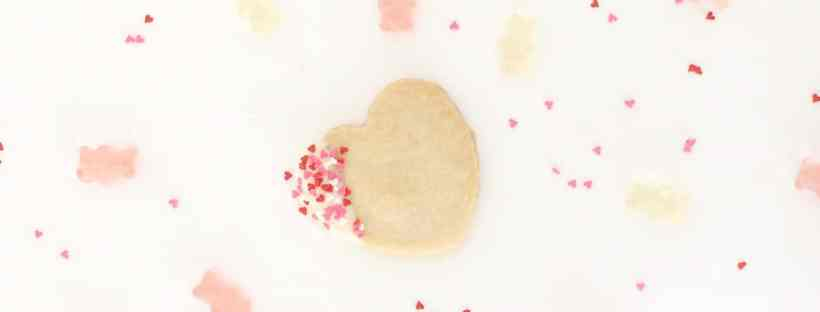 Shortbread cookie dipped in white chocolate and heart confetti.