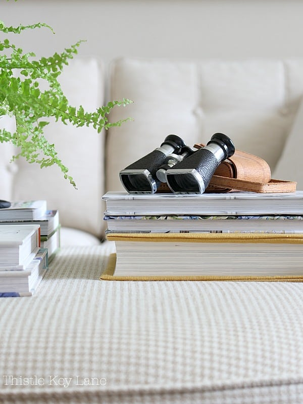 Style an ottoman with found objects like vintage binoculars.