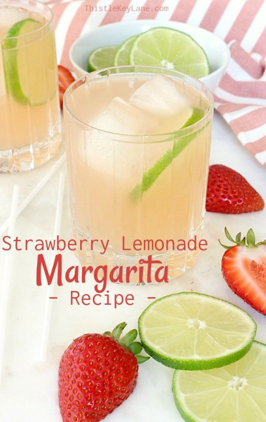 Margarita in a glass with ice surrounded with lime slices and strawberries.