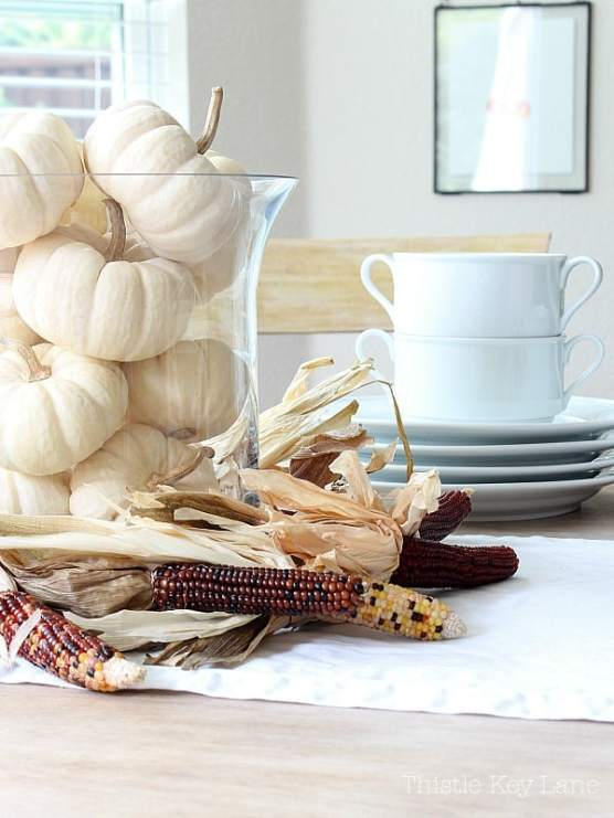 Mini Indian corn wreath with white pumpkins on a kitchen table.
