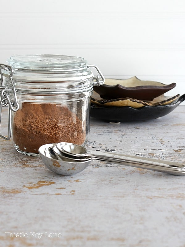 Clear jar with spices and a stack of measuring spoons and dishes.
