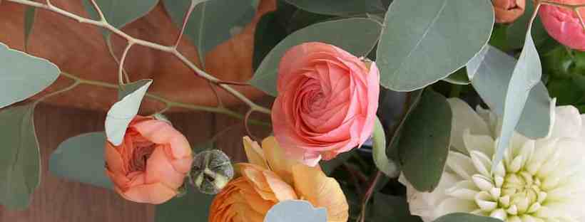 Peach, orange and yellow ranunculus with Dianthus and eucalyptus.
