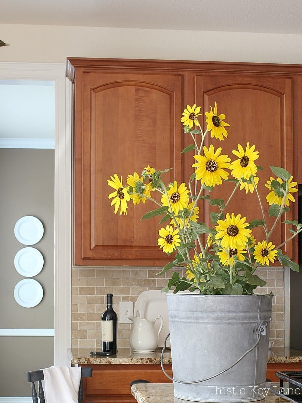 Happy fall sunflowers in a zinc bucket decorate the kitchen.
