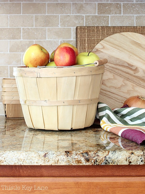 Bushel basket on kitchen counter with cutting boards.