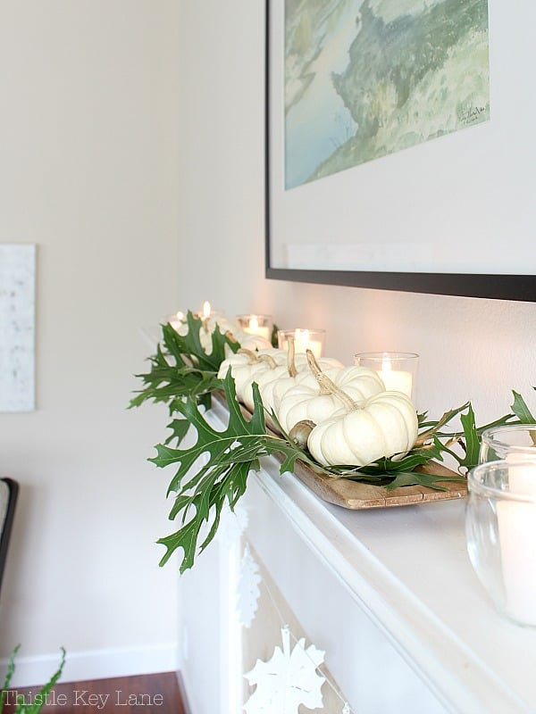 French baguette tray holding pumpkins and oak leaves on the mantel.