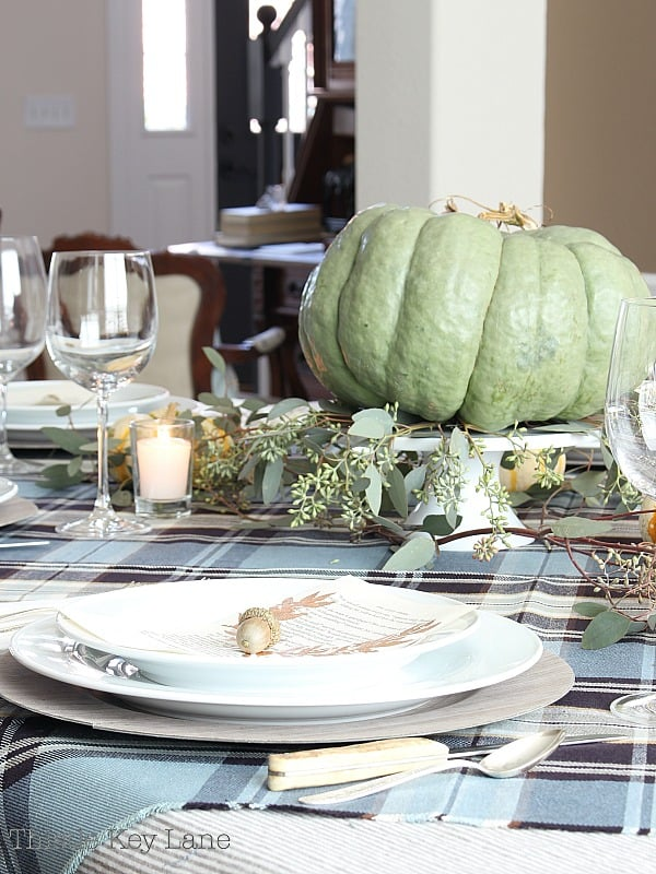 Tables cape with a green pumpkin, eucalyptus and plaid.