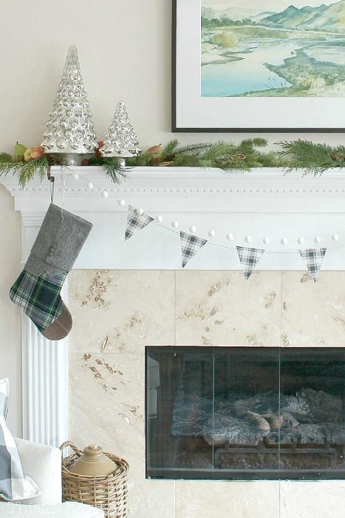Classic mantel with greenery, mercury trees and plaid.