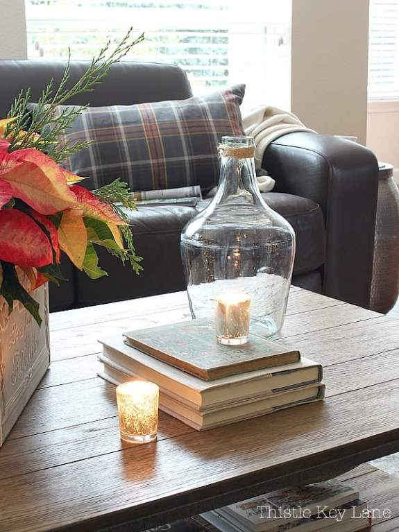 Coffee table with poinsettia, books, candles and bottle.