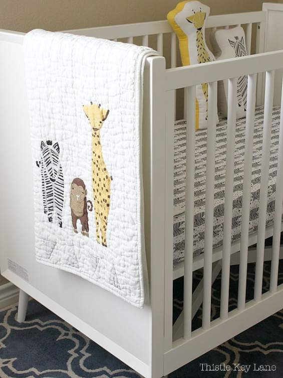 White baby bed with safari animal quilt.