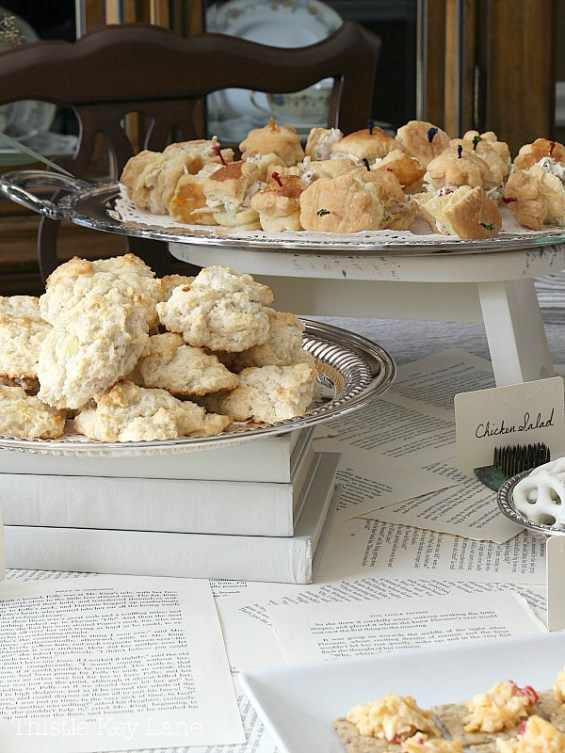 Silver trays loaded with scones and mini chicken salad puff pastry.
