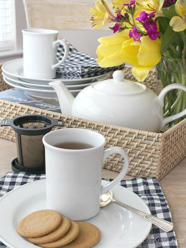 White tea mug, tea pot, checked napkins and tea infuser.