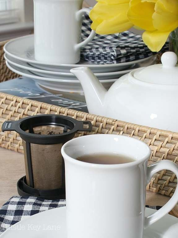 White dishes and wicker tray with check napkins.