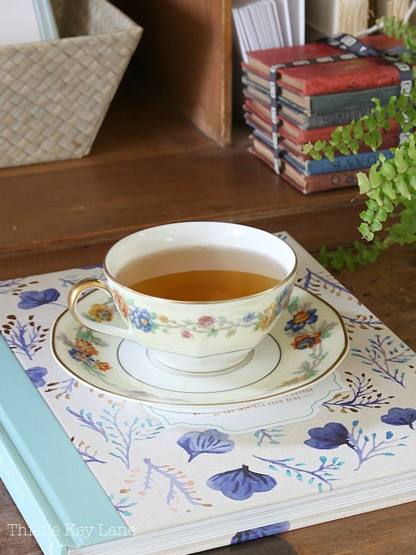 Flower china tea cup setting on top of decorating book.