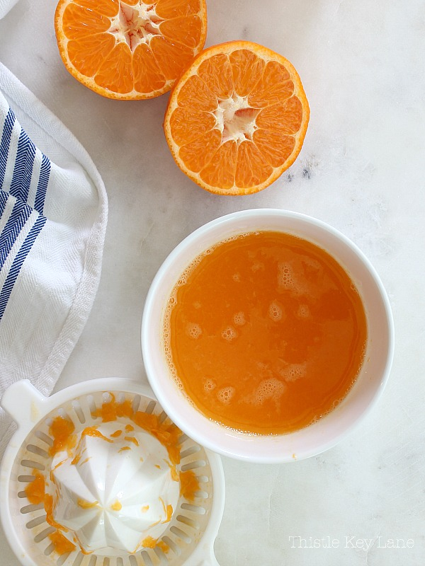 Fresh squeezed orange juice flat lay with oranges sliced.