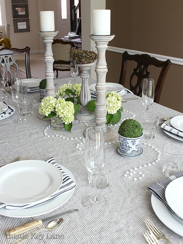 Centerpiece with tall candlesticks, green hydrangeas and a string of pompoms.