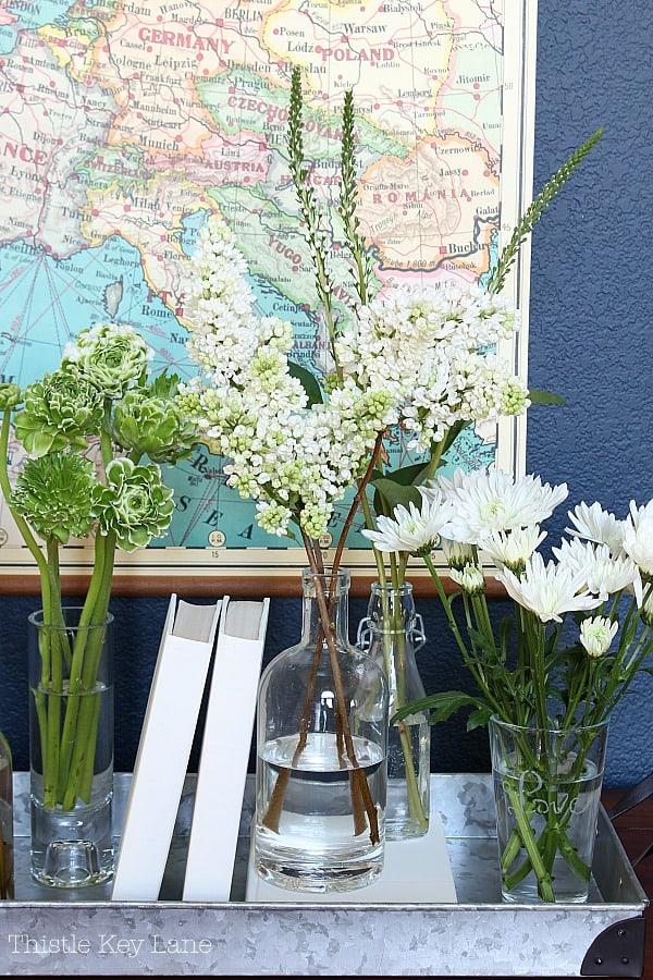 Variety of vases holding white flowers.