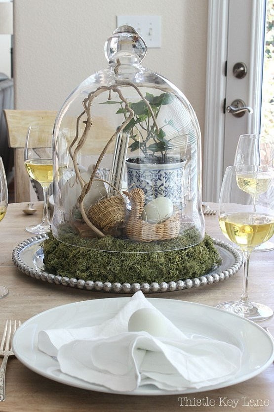 Spring tablescape with vintage cloche vignette of natural elements.