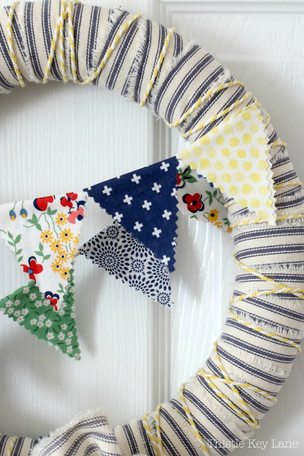 Close up of ticking wreath, cotton string and spring bunting.