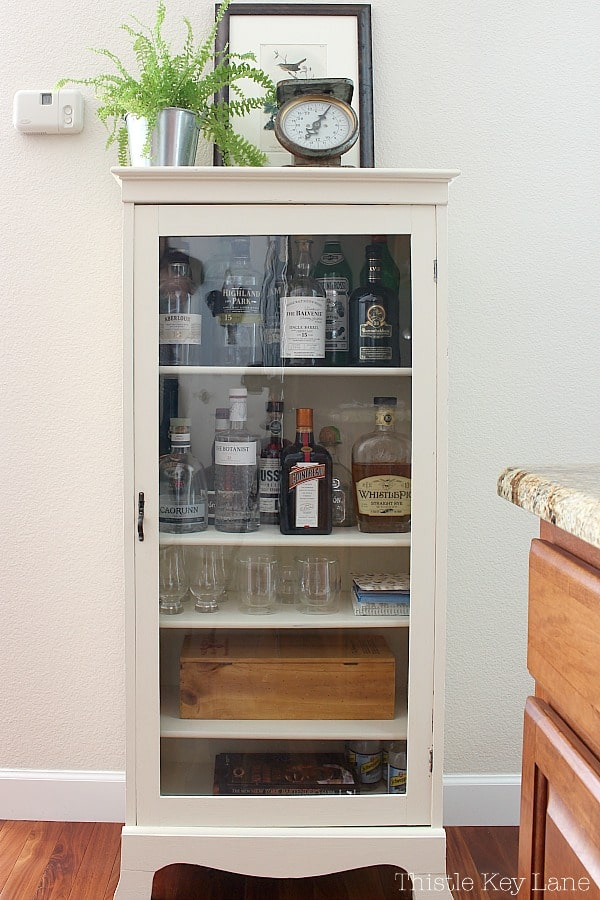 Curio cabinet repurposed as a liquor cabinet.
