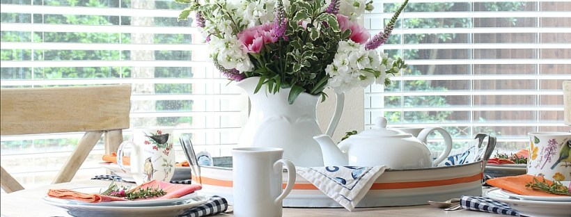 Table set for a tea party with pink and white flowers.