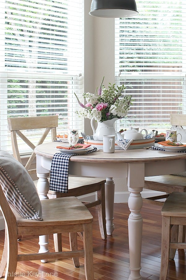 Cottage style white table set for tea with fresh flowers.