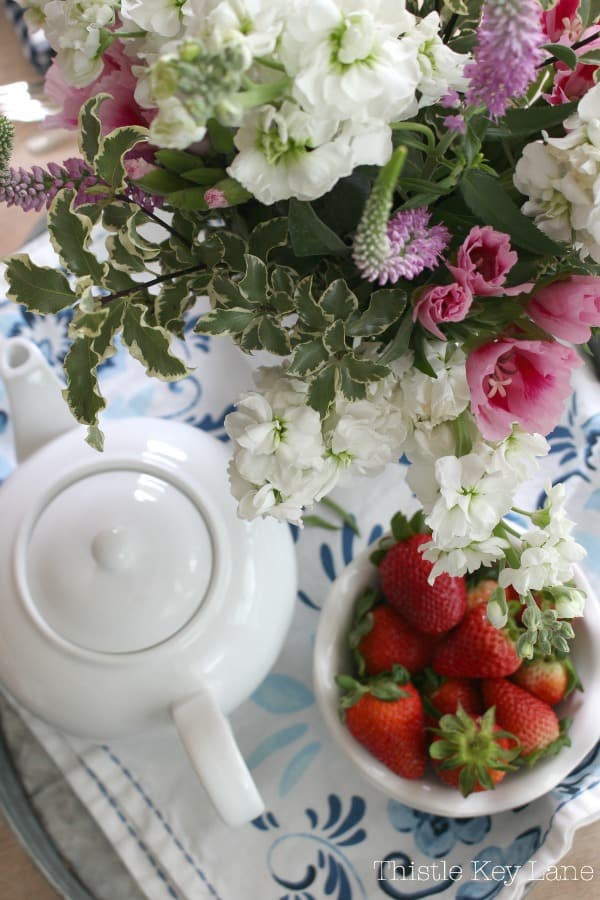 Pink and white flowers, a tea pot and bowl of strawberries on a tray.