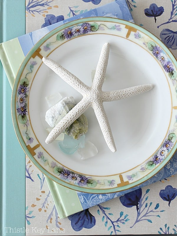 Plate with starfish and sea glass on top of decorating books.
