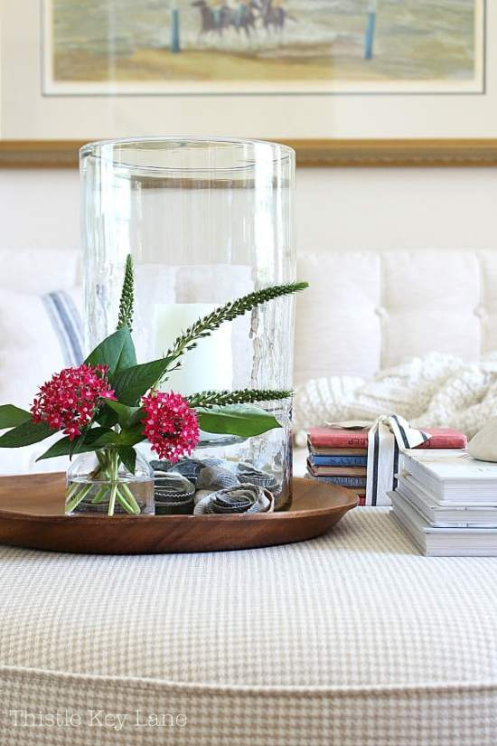 Red pentas in glass vase on a tray with books and candle.