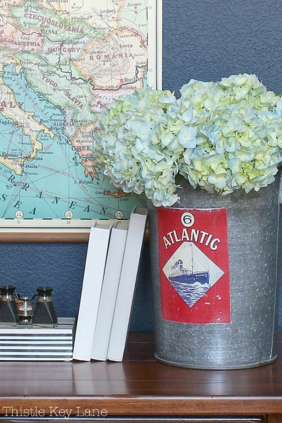 Vintage sap bucket holds hydrangea blooms against a blue wall with a map.