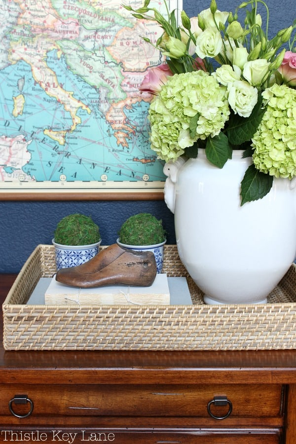 How to style an entry table tray by decorating in threes.