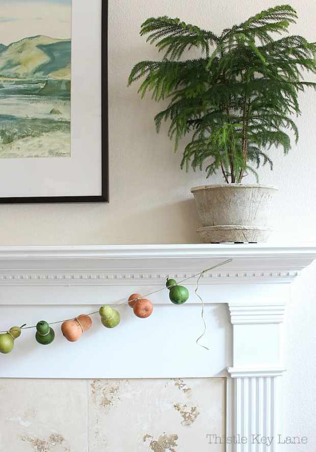 Neutral colors for a summer to fall mantel and a gourd garland.