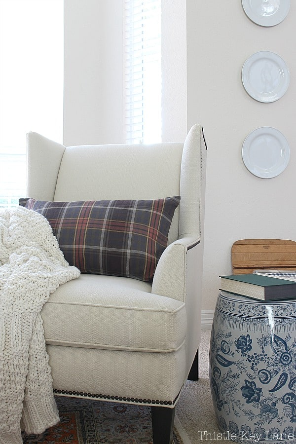 Simple Fall Home Decor Ideas - white wingback chair with dark plaid pillow.