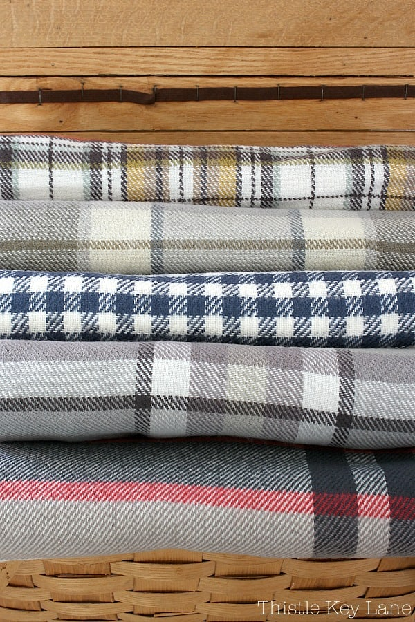 Stack of plaid throws in a picnic basket.