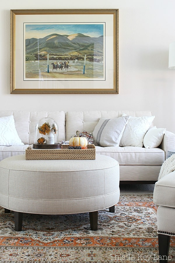 Simple Fall Home Decor Ideas - Neutral sofa and ottoman with fall accessories.