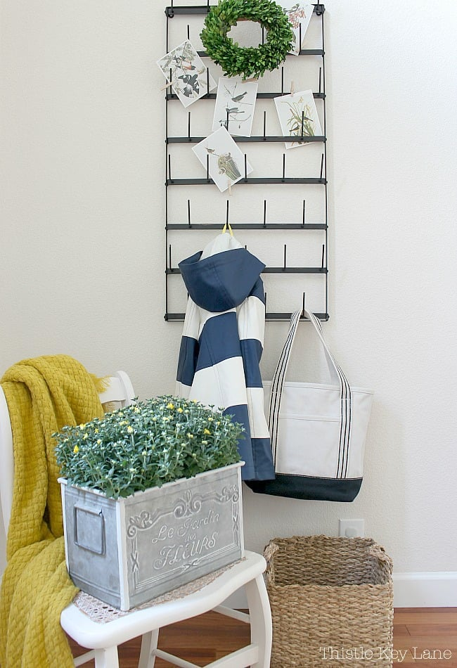 Fall Entryway With Navy And Yellow - chair with yellow throw and metal French planter with mums.